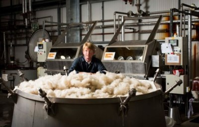Man on factory floor looking into large barrel of wool
