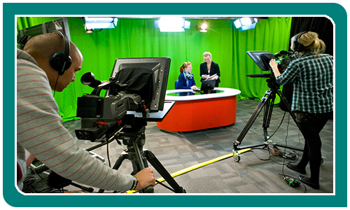 two people behind studio cameras looking at two people infront of a green screen