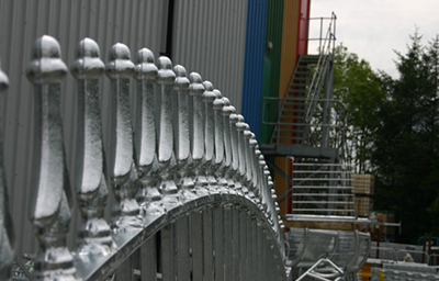 Close up of silver railings with a warehouse building behind