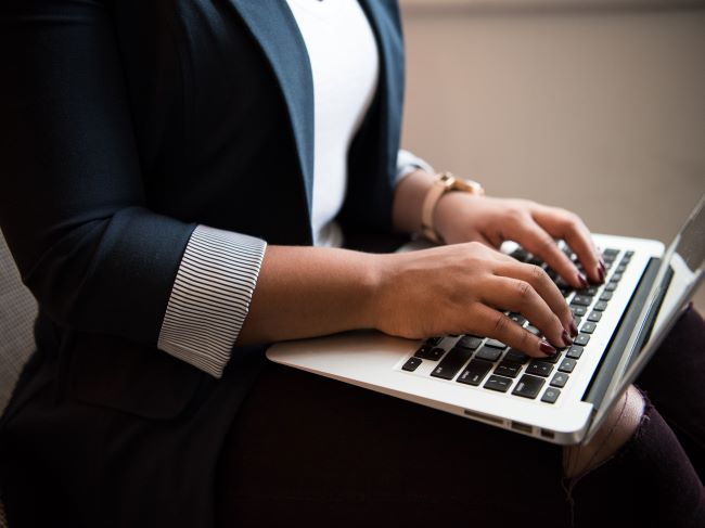 Close up image of a women typing on a laptop
