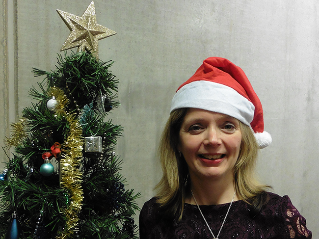 Dr Siobhán Jordan wearing a Santa hat and standing beside a decorated Christmas tree
