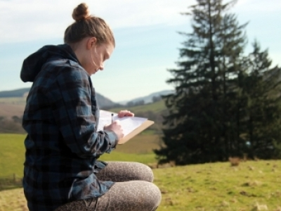 young woman sitting outdoors doing an environmental impact assessment
