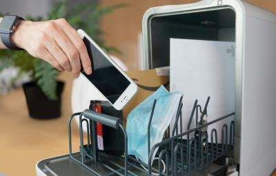 hand putting mobile phone into dishwasher to disinfect