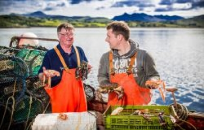 Two fishermen holding seafood on a boat