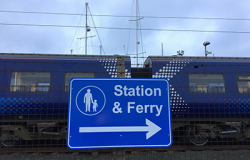 Blue sign infront of train carriages directing walkers to the station and ferry