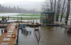Flooded garden with summer house and garden furniture