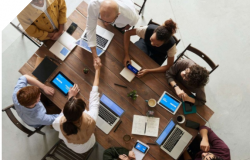 Group of people sitting around wooden table and working together with laptops.
