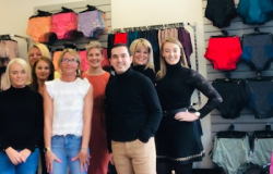 Group of seven people standing in line infront of medical lingerie