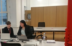 Two women sitting at desk looking at PC screen smiling